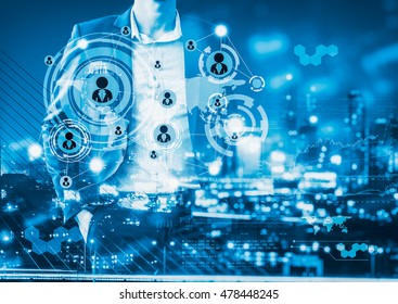 Digital business revolution concept. Double exposure of business man standing and city light with futuristic icons.