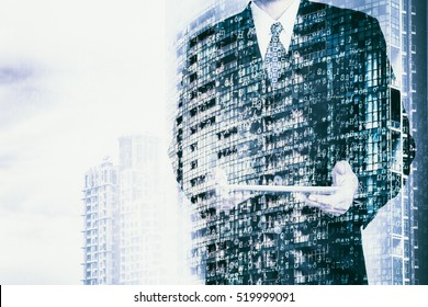 Digital business revolution concept. Double exposure of business man holding digital tablet and abstract digital coding on building. Blue tone.