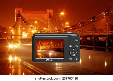 Digital camera capturing beautiful bridge illuminated by night