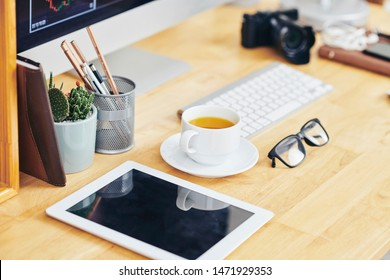 Digital camera with empty screen, cup of coffee, glasses and pot with glasses on office desk of entrepreneur