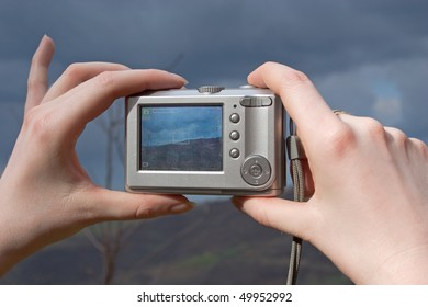 Digital camera in a hand taking photo of mountain landscape