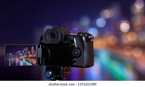 Digital camera over tripod on bokeh background of cityscape night light view of Singapore skyline at night
