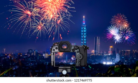 Digital camera over tripod on blur of firework with cityscape night light view of Taipei. Taiwan city skyline at twilight time