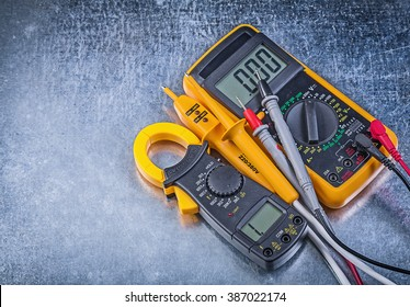Digital clamp meter electric tester multimeter on metallic background.