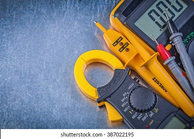 Digital clamp meter electrical tester multimeter on metallic background.