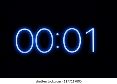Digital clock timer stopwatch display showing 1 one second remaining in glowing blue numbers. Emergency, urgency, out of time concept.