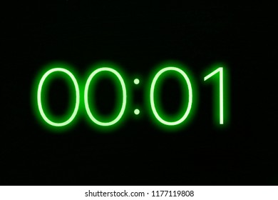 Digital clock timer stopwatch display showing 1 one second remaining in glowing green numbers. Emergency, urgency, out of time concept.