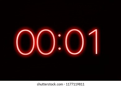 Digital clock timer stopwatch display showing 1 one second remaining in glowing red numbers. Emergency, urgency, out of time concept.