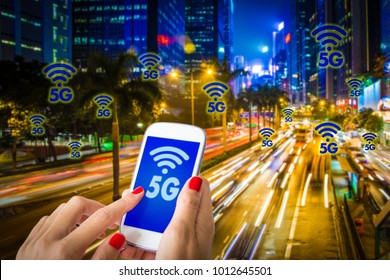 Digital composite of 5G , a woman hand using smartphone with blurry modern city on the background. Hong Kong busy city and High speed mobile web technology concept.