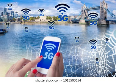 Digital composite of 5G , a woman hand using smartphone with blurry modern city on the background. London city and High speed mobile web technology concept.