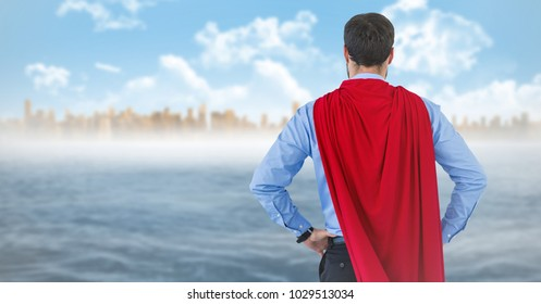 Digital composite of Back of business man superhero with hands on hips against skyline and water