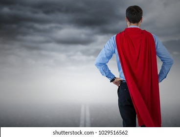 Digital composite of Back of business man superhero with hands on hips against road and stormy sky