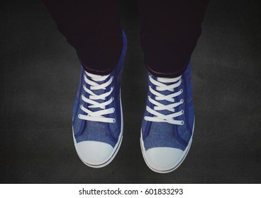 Digital composite of Blue shoes on concrete against a black floor