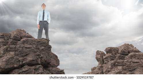 Digital composite of Business man hand in pocket on rocks against clouds with flare