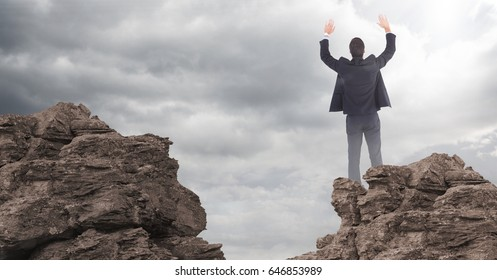 Digital composite of Business man hands in air on rocks against clouds with flare