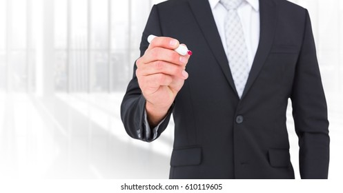 Digital composite of Business man mid sections with pen against blurry window