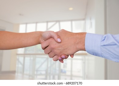 Digital composite of Business people shaking hands against office background