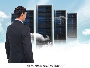 Digital composite of Business Standing looking at folders against blue sky
