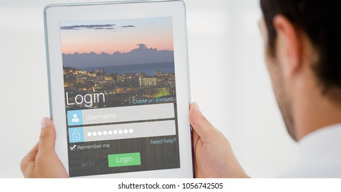 Digital composite of Businessman holding tablet PC with log in page on screen