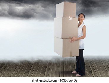 Digital composite of Businesswoman holding boxes with clouds