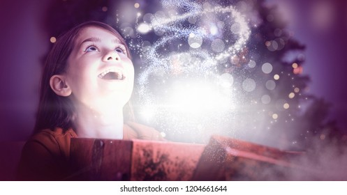 Digital composite of Excited girl opening magical Christmas gift box with sparkling light