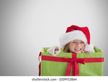 Digital composite of Girl against grey background inside gift box with Santa Christmas hat