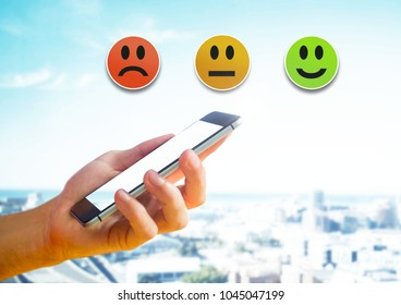 Digital composite of Hand holding phone and Feedback smiley satisfaction icons