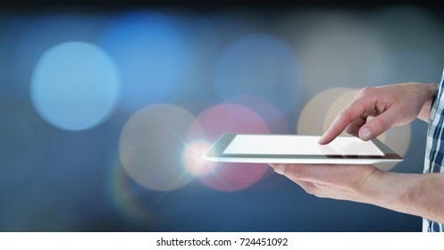 Digital composite of Hand holding tablet with glow