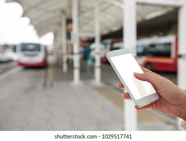 Digital composite of Hand with mobile in the bus station