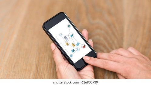 Digital composite of Hand using smart phones with icons on screen