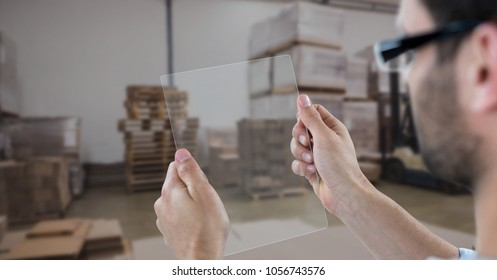 Digital composite of Hands photographing through transparent device in warehouse