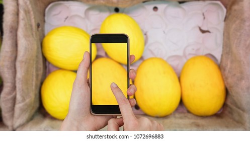 Digital composite of Hands taking picture of mangoes with mobile phone in grocery store