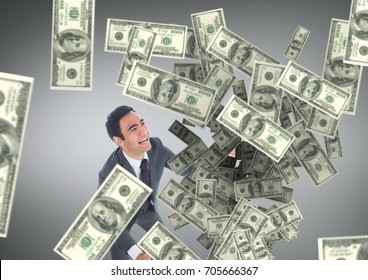 Digital composite of Happy business man looking at money rain against grey background