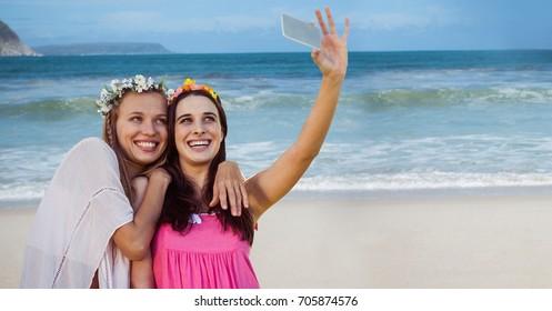 Digital composite of Hippie girls taking selfie against beach