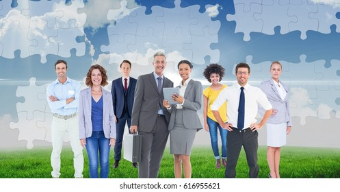 Digital composite of Digital composite image of business people standing against puzzle background