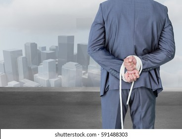 Digital composite image of a businessman with his hands tied behind the back against cityscape in the background