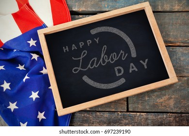 Digital composite image of happy labor day text with blue outline against high angle view of american flag with chalkboard