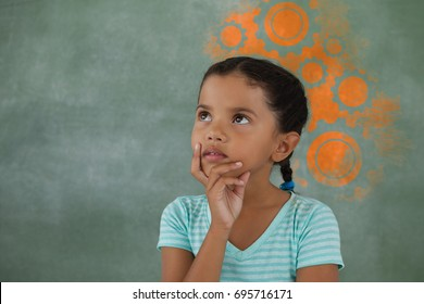 Digital composite image of white gears on blue spray paint against thoughtful young girl
