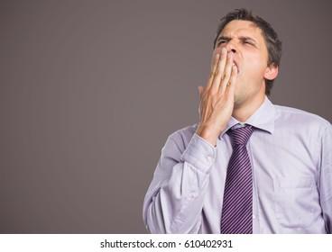 Digital composite of Man in lavender shirt yawning against brown grey background