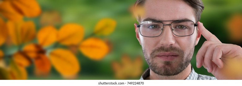 Digital composite of Man's face in forest with leaves and glasses