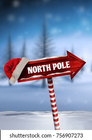 Digital composite of North Pole text and Wooden signpost in Christmas Winter landscape with Santa hat