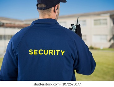 Digital composite of Rear view of security guard using radio against house