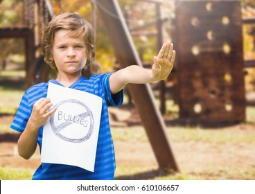 Digital composite of Sad boy holdingn anti bullying sign against playground
