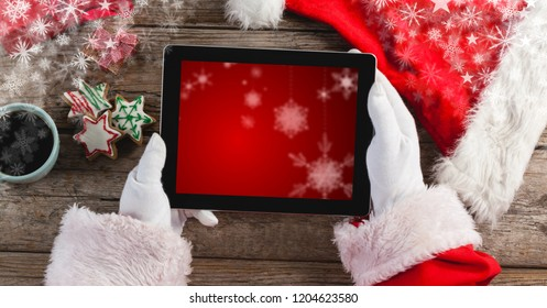Digital composite of Santa holding tablet with snowflakes