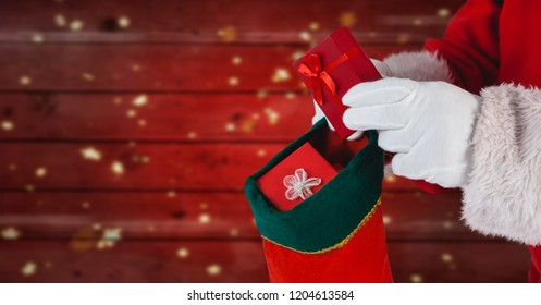 Digital composite of Santa putting gifts in stocking with red wood