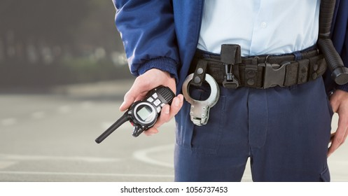 Digital composite of Security guard lower body with walkie talkie against blurry street