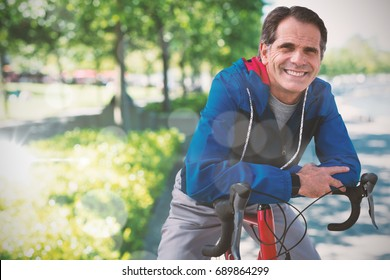 Digital composite of senior man with his bike against blur view of park