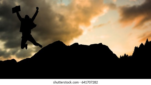 Digital composite of Silhouette businessman jumping on mountain during sunset