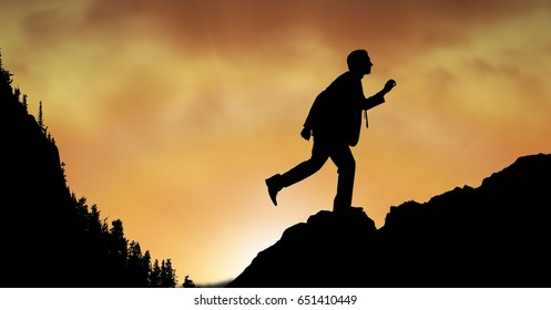 Digital composite of Silhouette businessman walking on mountain during sunset