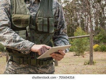 Digital composite of Soldier man using a tablet against field